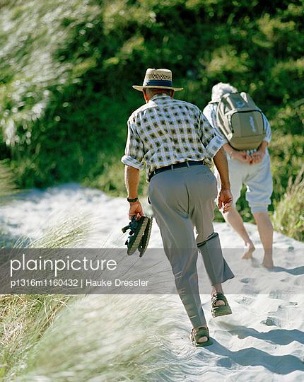 Altes Paar wandert über eine Düne zum Wharariki Beach, Nordwestküste, Südinsel, Neuseeland - p1316m1160432 von Hauke Dressler