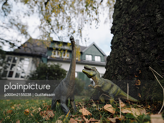 Dinosaur figurines in garden in autumn - p300m2155038 by Gustafsson