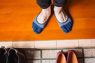 A man's feet in socks by a row of shoes.  - p1100m1531129 by Mint Images