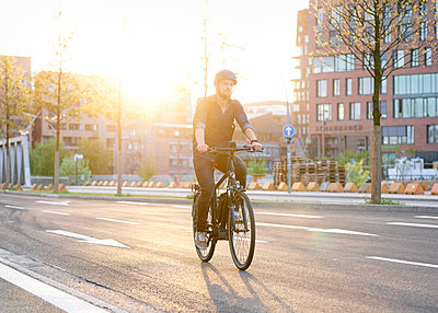Bicycle courier riding an electric bike - p1124m2053008 by Willing-Holtz
