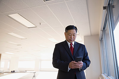 Male architect using cell phone in empty office - p1192m1403531 by Hero Images