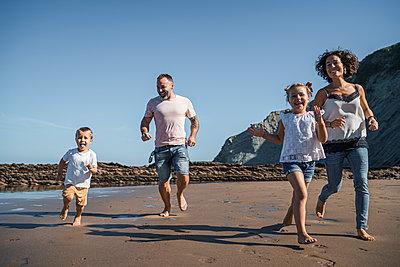 Family having fun while running on beach against sky - p300m2257263 by SERGIO NIEVAS