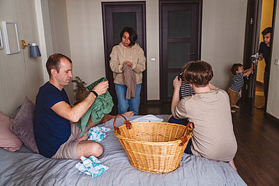 Family doing laundry in bedroom at home - p300m2277687 by Katharina und Ekaterina