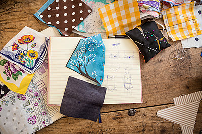 Sketchbook and cloth samples on work desk - p300m998489f by Dieter Schewig