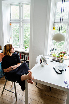 Young woman sitting with feet up in apartment - p352m2119888 by Lena Katarina Johansson
