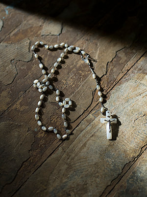 Rosary on wooden floor - p945m1465922 by aurelia frey