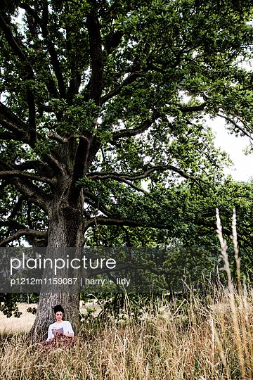 Junge Frau sitzt unter einem Baum - liest - p1212m1159087 von harry + lidy