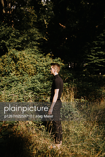 Young man standing at the edge of the forest - p1267m2259710 by Jörg Meier