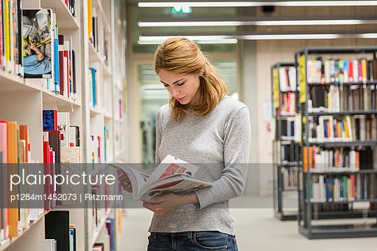 Studentin blättert in einem Fachbuch - p1284m1452073 von Ritzmann
