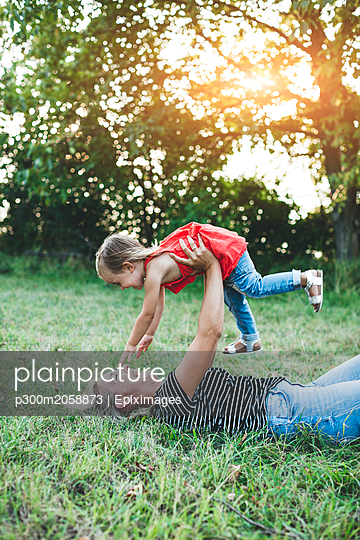 Happy mother playing with daughter on meadow - p300m2058873 von Epiximages
