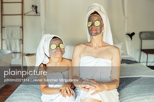 Mother and daughter in towel with facial mask and slice of cucumber on eyes sitting at home - p300m2221514 by Javier Sánchez Mingorance