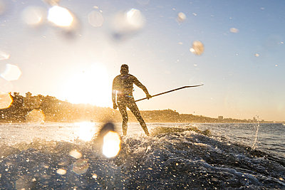 Surfer holding pole while surfing in sea during sunset - p1166m1414555 by Cavan Images