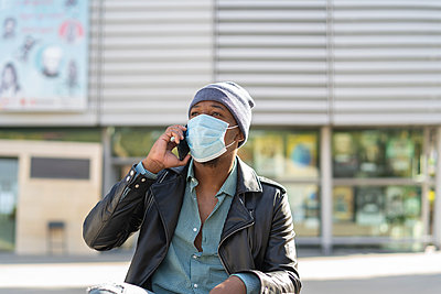 young african man walking through the city wearing the mask - p1166m2218245 by Cavan Images