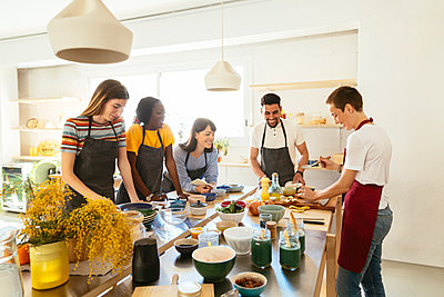 Friends and instructor in a cooking workshop preparing food - p300m1587203 by Bonninstudio