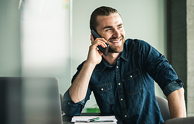 Smiling young businessman on cell phone in office - p300m2043168 by Uwe Umstätter