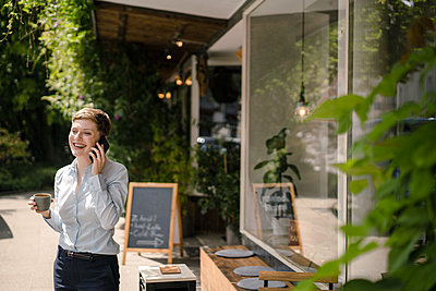 Happy businesswoman using cell phone at a cafe - p300m2140877 by Kniel Synnatzschke