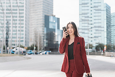 Businesswoman talking on smart phone while walking in city - p300m2266400 by COROIMAGE