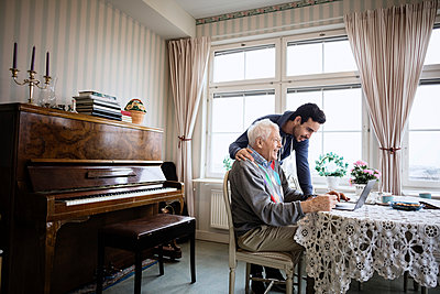Happy man using laptop with caretaker in nursing home - p426m1131145f by Maskot