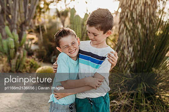 Cheerful brothers embracing and smiling in sunny cactus garden - p1166m2136656 by Cavan Images