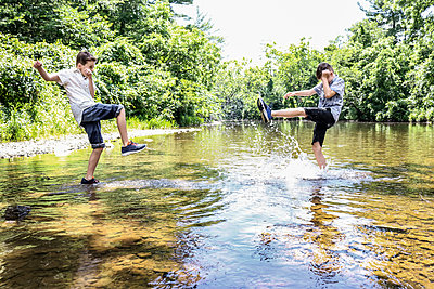 Two boys have fun in shallow water - p1019m1462179 by Stephen Carroll