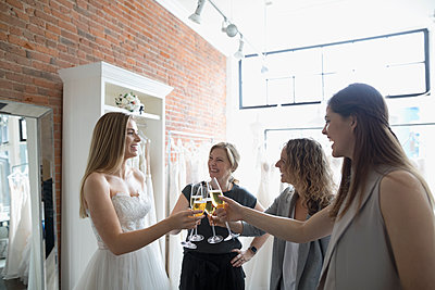 Bride, mother and friends toasting champagne at wedding dress fitting at bridal boutique - p1192m1583306 by Hero Images
