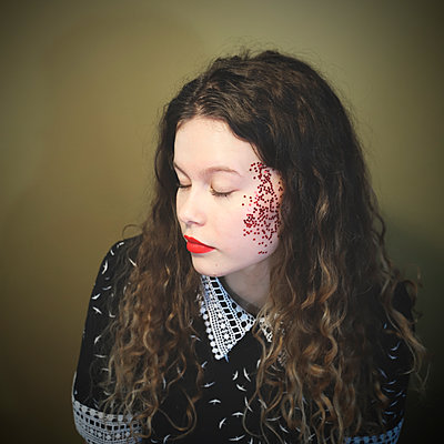 Young woman with glitter on her face, portrait - p1521m2231494 by Charlotte Zobel