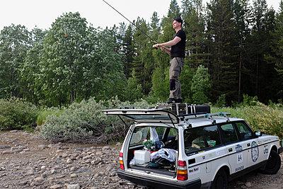 Angler steht auf einem Autodach - p236m1332808 von tranquillium