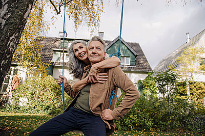 Happy woman embracing senior man on a swing in garden - p300m2155231 by Gustafsson