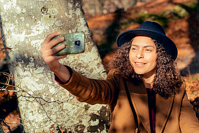 Woman smiling while taking selfie through mobile phone in forest - p300m2240469 by Francesco Morandini