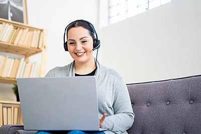 Smiling female freelancer wearing headphones while working at home - p300m2275329 by Giorgio Fochesato