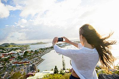 Woman taking picture of coast landscape - p429m817379 by Matt Dutile