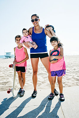 Mother and daughters holding kettle bells at beach - p555m1305540 by Peathegee Inc
