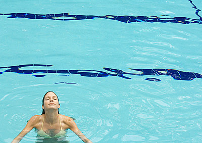 Woman standing in pool - p62316098f by Matthieu Spohn