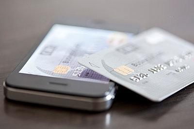 Credit card resting on smartphone - p623m1487563 by Gabriel Sanchez