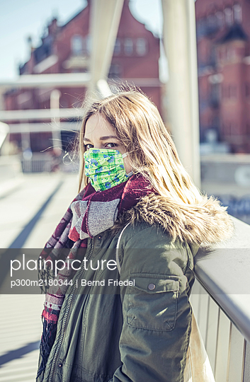 Portrait of young woman wearing mask on a bridge in the city - p300m2180344 by Bernd Friedel