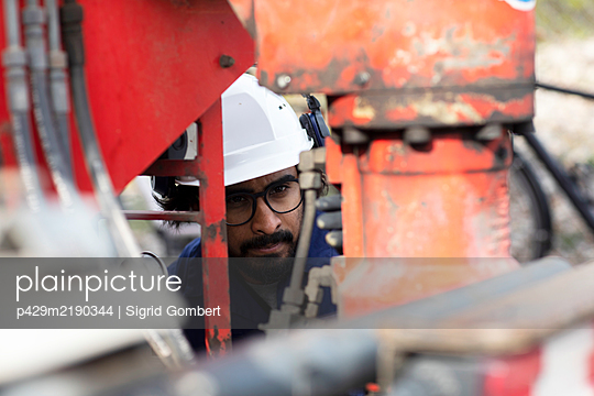 Bearded man wearing eyeglasses and white hard hat working on construction site.  - p429m2190344 by Sigrid Gombert