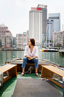 Female tourist sitting on boat against buildings - p1166m1150889 by Cavan Images