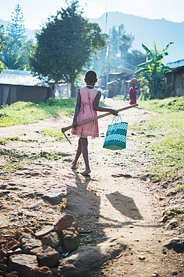 Africa, Uganda, Girl with bag and rake in a village - p1167m2283461 by Maria Schiffer