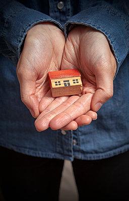 Hände halten ein Miniatur Holzhaus - p1248m1582928 von miguel sobreira