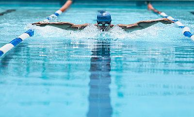 Young Caucasian male swimmer swimming butterfly stroke in swimming pool - p1315m2091032 by Wavebreak