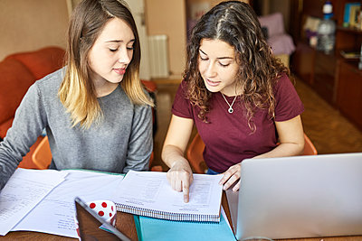 Two female students at desk working and learning together - p300m1587155 by Josep Rovirosa