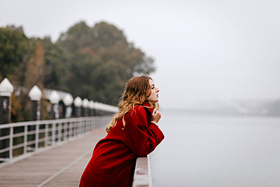 Portrait of young woman wearing red coat, leaning on railing on rainy day - p300m2160300 von Tania Cervián