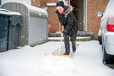 Germany, Grevenbroich, woman shoveling snow in front of house - p300m998932f by Frank Röder