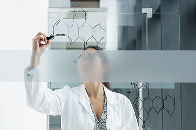 Medical student drawing atoms on glass wall in classroom - p429m2145540 by suedhang photography
