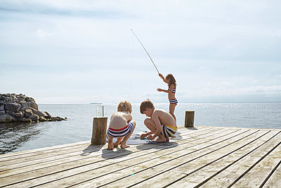 Boys and girl fishing off sunny lakeside dock - p1023m1172725 by Francis Pictures