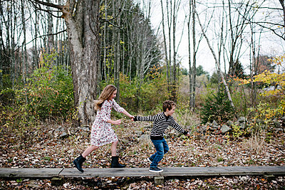 Playful siblings holding hands while running against trees at park - p1166m1555646 by Cavan Images