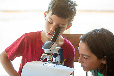 Boy looking into microscope with girl looking on - p1166m2236928 by Cavan Images