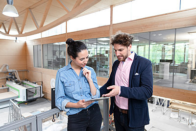 Male entrepreneur explaining strategy to female colleague over digital tablet in factory - p300m2265987 by Florian Küttler