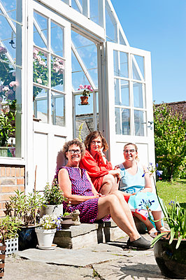 Three women sitting in front of greenhouse - p312m1113893f by Rebecca Wallin