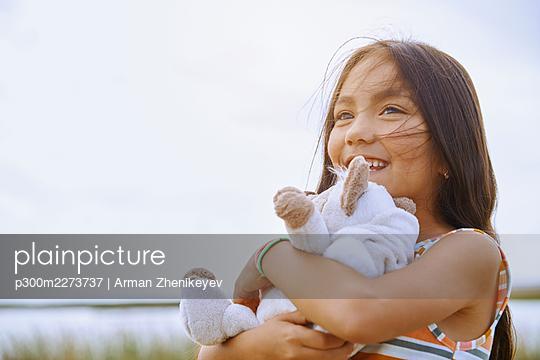 Cute girl looking away while holding stuffed teddy bear - p300m2273737 by Arman Zhenikeyev